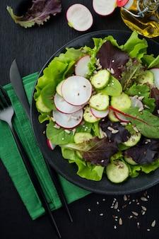 Salat mit frischen radieschen, rucola, rüben, mangold, sonnenblumenkernen, leinsamen und sesam auf einer schwarzen oberfläche. selektiver fokus. draufsicht. speicherplatz kopieren.