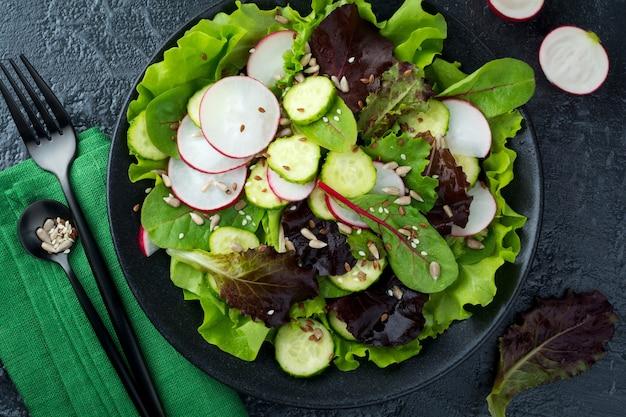 Salat mit frischen radieschen, rucola, rüben, mangold, sonnenblumenkernen, leinsamen und sesam auf einer schwarzen oberfläche