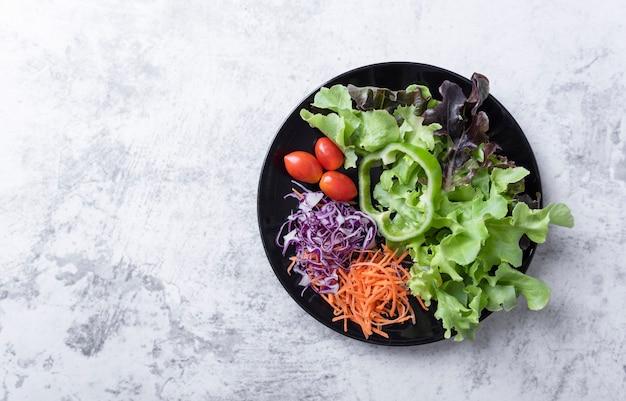 Salat mit frischen tomaten, karotten, salat auf tischhintergrund. gesundes veganes essen. ansicht von oben. banner