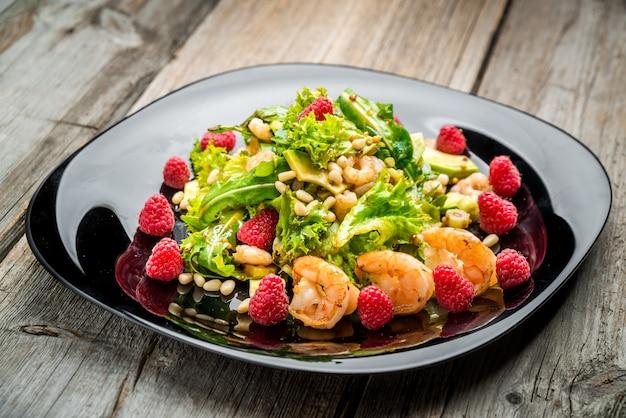Salat mit garnelen, avocado und frischen himbeeren auf einem schwarzen teller