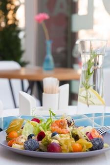 Salat mit garnelen und maca-käse, physalis, trauben, salat