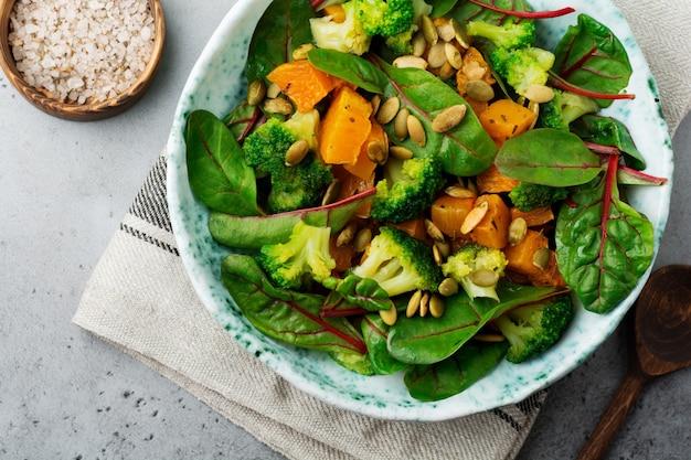 Salat mit gebackenem kürbis, mangold, brokkoli und kürbiskernen in keramikplatte auf stein oder betontisch. rustikaler stil.