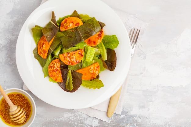 Salat mit gebackenem kürbis mit senf-honig-dressing in einem weißen teller, kopierraum, draufsicht. gesundes veganes lebensmittelkonzept.