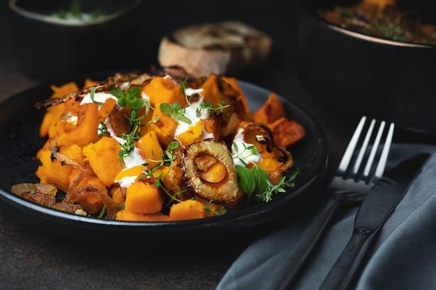 Salat mit gebackenem kürbis, thymian, gerösteten zwiebeln und joghurtwurst, ein köstliches herbstgericht. auf dunklem hintergrund. selektiver fokus