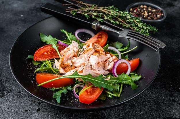 Salat mit gebratenem lachsfiletsteak, frischem salatrucola und tomate in einem teller. schwarzer hintergrund. ansicht von oben.