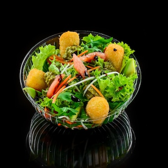 Salat mit gebratenem speck, gemüse und mit nuggets auf schwarzem grund