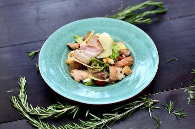 Salat mit gebratenem speck, parmesan, kirschtomaten und crackern