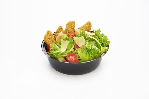 Salat mit gebratenen hähnchenstreifen und geschnittenem parmesan in einer plastikschüssel zum mitnehmen
