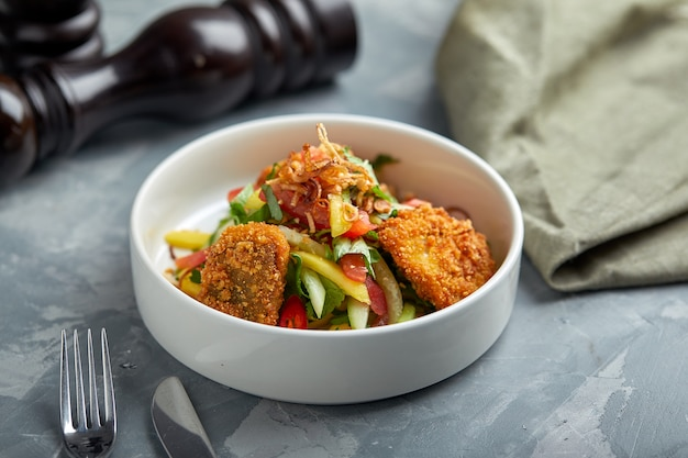 Salat mit gebratenen hühnernuggets und gemüse