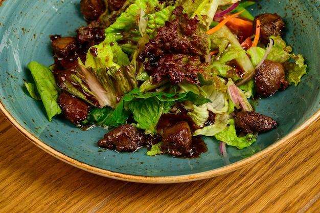 Salat mit gebratenen pilzen, tomaten und salat auf einem holztisch, draufsicht