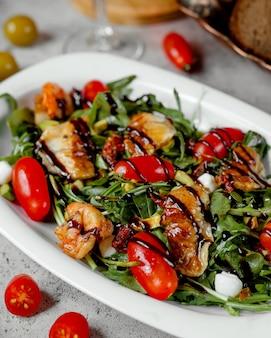 Salat mit gegrillten garnelen und tomaten auf dem tisch