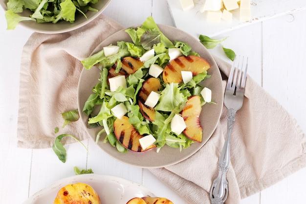 Salat mit gegrillten pfirsichen, rucola und mozzarella