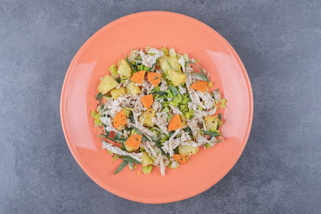 Salat mit gehacktem huhn auf orangefarbenem teller.