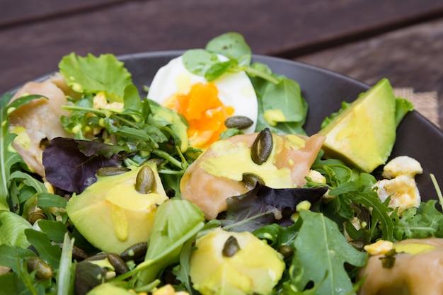 Salat mit gemüse, eiern und grüns auf holztisch
