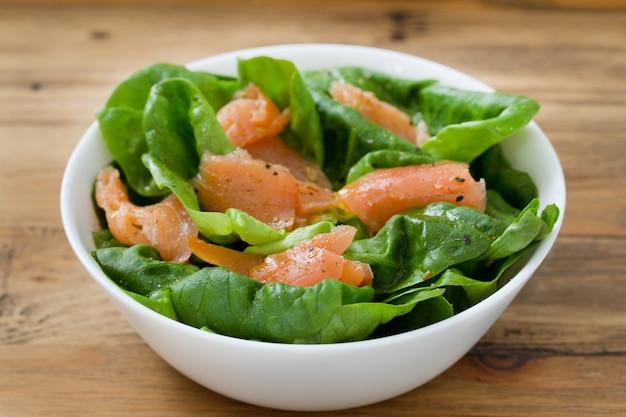 Salat mit geräuchertem lachs auf weißer schüssel auf brauner holzoberfläche
