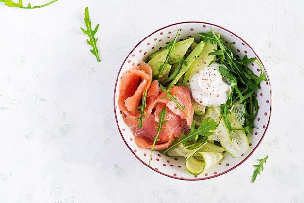 Salat mit gesalzenem lachs, avocado und gurken mit frischkäse in weißer schüssel