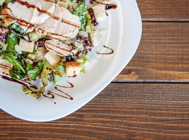 Salat mit gurke und huhn und kopfsalat auf einem hölzernen