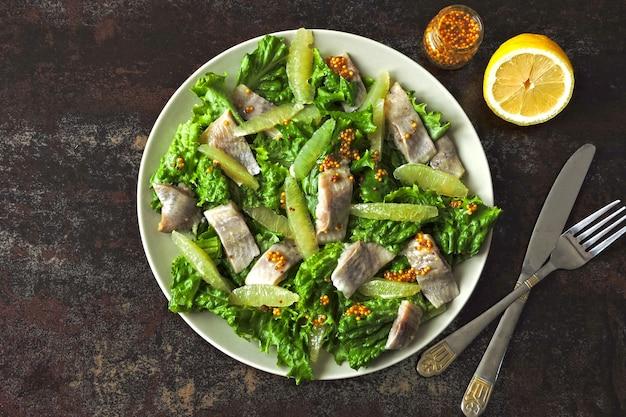Salat mit hering und zitronenfilet. paläo-diät, keto-diät, pegan-diät. gesunder fitness-salat mit zitrone und fisch.