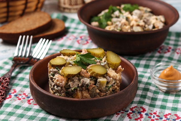 Salat mit hühnerleber, omelett und eingelegten gurken auf braunem teller, horizontalformat