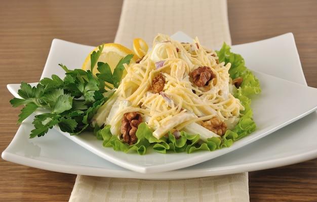 Salat mit käse und apfel, walnüssen und joghurt auf salatblättern mit zitrone