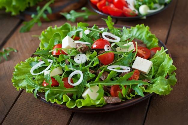 Salat mit kalbsscheiben, rucola, tomaten und feta