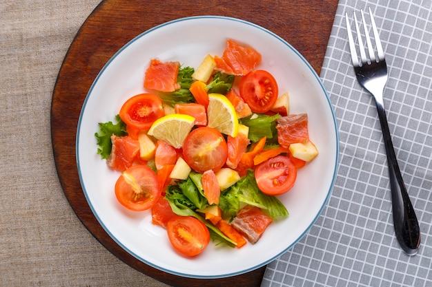 Salat mit kaltem lachs und kirschtomaten in einem teller auf einer grauen oberfläche auf einem holzständer einen ständer neben einer gabel