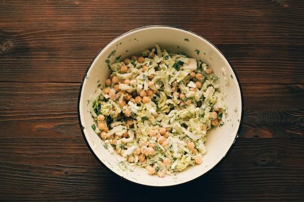 Salat mit kichererbsen in einer schüssel auf einem holztisch, draufsicht