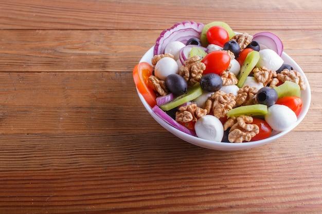 Salat mit kirschtomaten, mozzarellakäse, oliven, kiwi und walnüssen auf braunem holztisch.