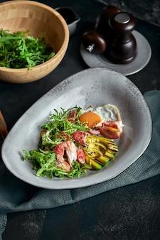 Salat mit krabben und avocado auf einer dunkelheit. arugulasalatblätter gewürzt mit soße auf weißwein mit krebsfleisch und gegrillter avocado in der weichzeichnung. ansicht von oben