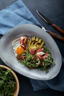 Salat mit krabben und avocado auf einer dunkelheit. arugulasalatblätter gewürzt mit soße auf weißwein mit krebsfleisch und gegrillter avocado in der weichzeichnung.