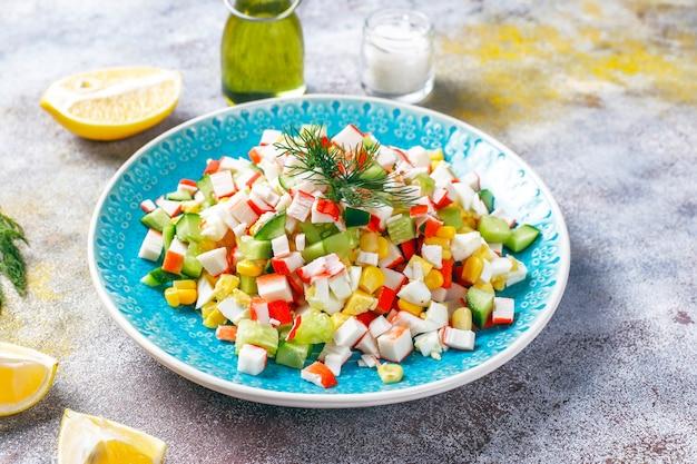Salat mit krabbenstäbchen, eiern, mais und gurke.