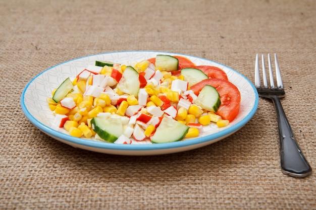 Salat mit krabbenstäbchen, gekochtem mais und frisch geschnittenen tomaten und gurken auf teller mit gabel auf sackleinen