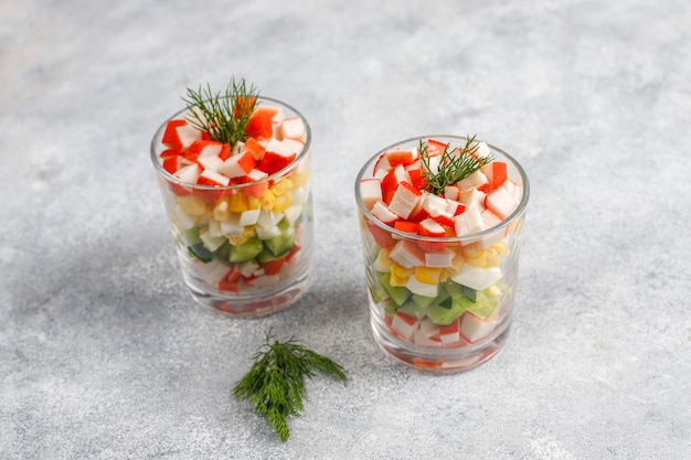Salat mit krabbenstangen, eiern, mais und gurke.