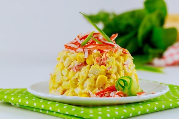 Salat mit krabbenstangen, gurke, eiern auf weißem teller.