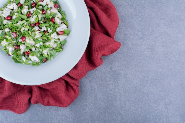 Salat mit kräutern, obst und gemüse in einer platte
