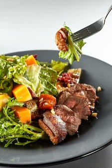 Salat mit kürbis, gegrillter fleischente und frischem grünem salat auf einem teller und gabel mit salat in der luft