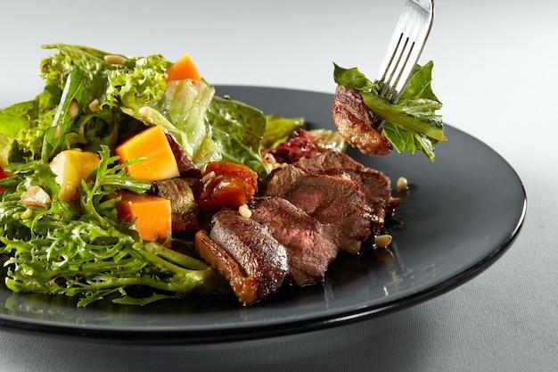 Salat mit kürbis, gegrillter fleischente und frischem grünem salat auf einem teller und gabel mit salat