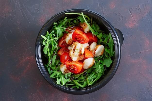 Salat mit mozzarella, tomate und rucola zum mitnehmen