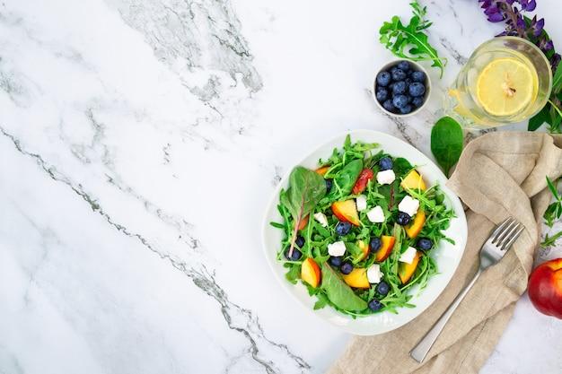 Salat mit nektarinen blaubeeren rucola-spinat und feta-käse auf weißem marmorhintergrund