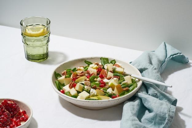 Salat mit nüssen. spinat mit äpfeln, pekannüssen und feta. hartes licht, schatten, seitenansicht