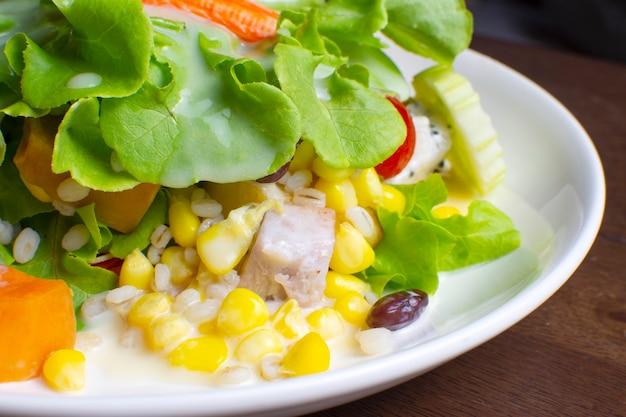 Salat mit obst und frischem gemüse mit salatdressing in einer weißen schale auf holztisch gekrönt