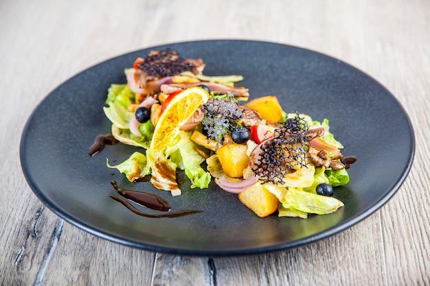 Salat mit obst und hühnchen in pikanter sauce