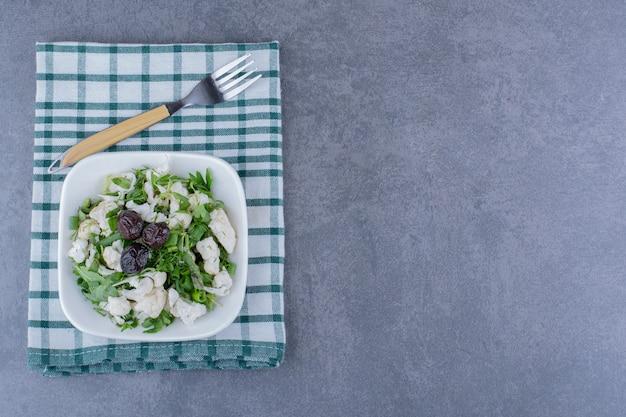 Salat mit oliven, kräutern und blumenkohl in einer keramiktasse