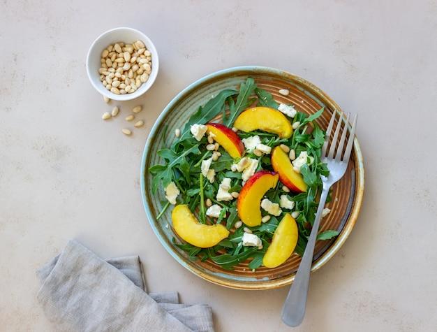 Salat mit pfirsich, rucola, käse, nüssen und honig. gesundes essen. vegetarisches essen. rezept.