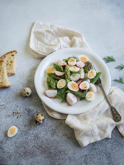 Salat mit rettich, wachtelei, grünem spargel und dill in einer weißen platte