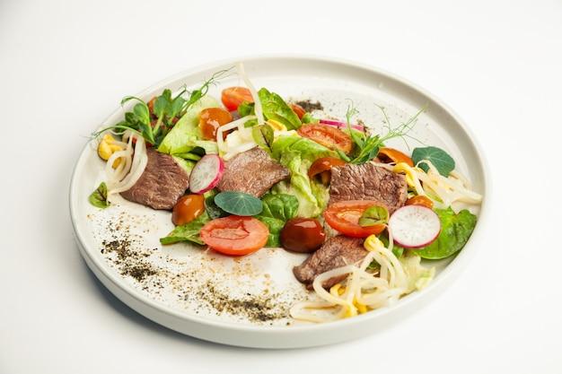 Salat mit rindfleisch tataki auf einem teller.