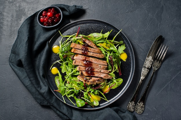 Salat mit rindfleischsteak, rucola und mangold auf einem schwarzblech.