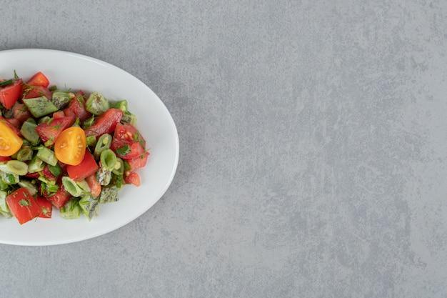 Salat mit roten kirschtomaten und bohnen in einer keramikplatte
