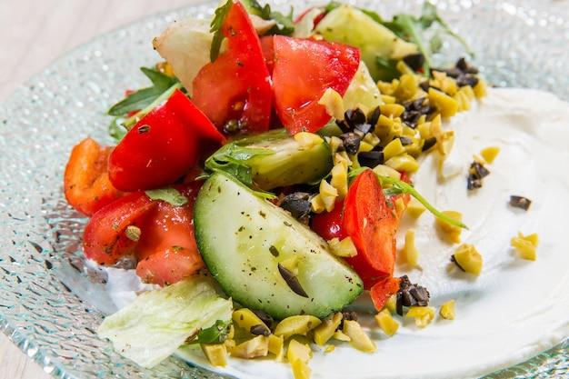 Salat mit roten tomaten, gurken und oliven in der glasplatte auf leuchttisch in einem restaurant