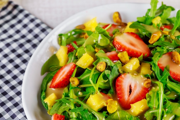 Salat mit rucola, erdbeeren, mango und pistazien